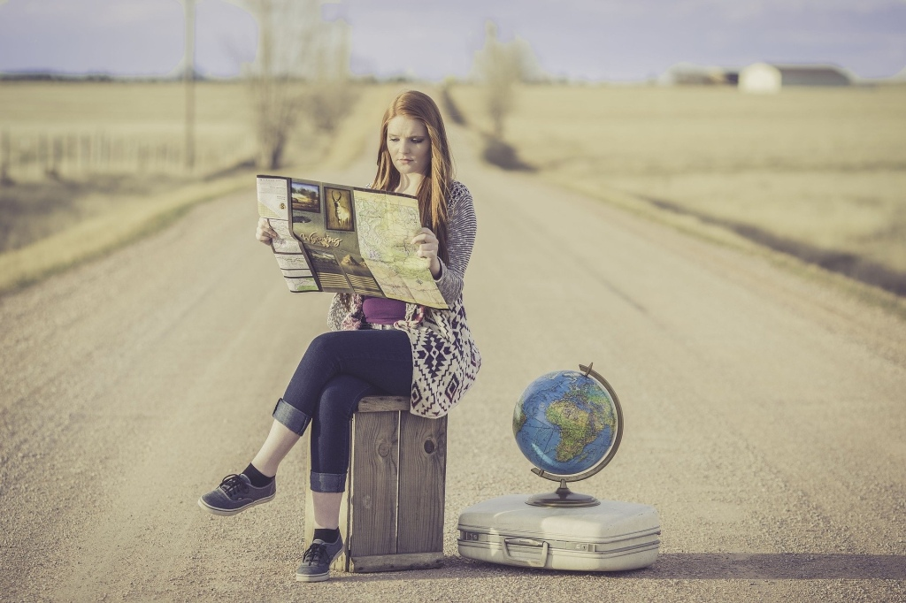 Woman sitting in road looking at map